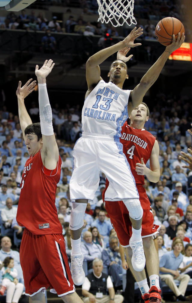 North Carolina's J.P. Tokoto (13) goes to the basket against Davdison's Jake Belford, left, and Tyler Kalinoski (4) during the first half of an NCAA college basketball game in Chapel Hill, N.C., Saturday, Dec. 21, 2013. (AP Photo/Ellen Ozier)
