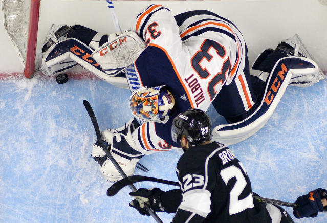 Los Angeles Kings right wing Dustin Brown, below, puts the puck over the line past Edmonton Oilers goaltender Cam Talbot with seconds to go in the third period of an NHL hockey game Saturday, Feb. 24, 2018, in Los Angeles. The goal was called back for goalie interference. The Oilers won 4-3. (AP Photo/Mark J. Terrill)