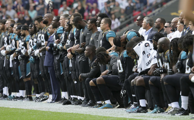Jaguars players lock arms and kneel in September days after President Donald Trump blasted the NFL. (AP)