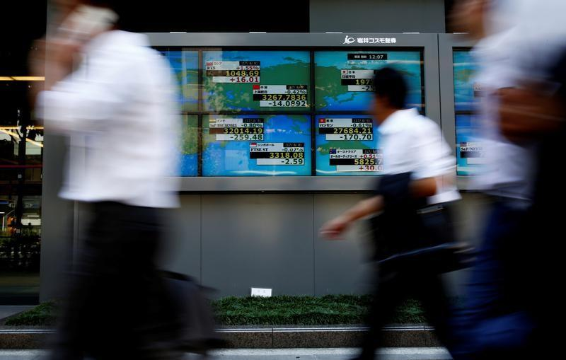 People walk past an electronic board showing Japan's Nikkei average outside a brokerage at a business district in Tokyo