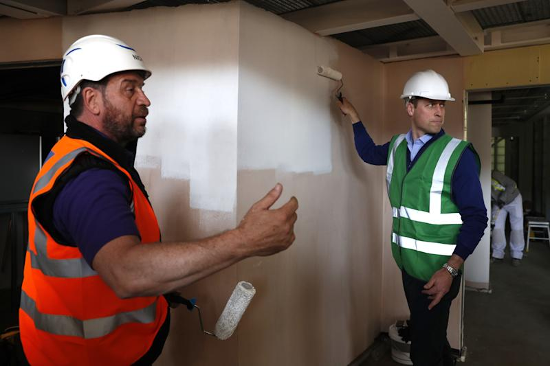 LONDON, UNITED KINGDOM - MAY 15: Britain's Prince William, Duke of Cambridge (R) and presenter Nick Knowles paint a wall as he joins the crew of DIY SOS on a major project to build a community centre, in support of the people affected by the devastating fire at Grenfell Tower, on May 15, 2018 in London, England. (Photo by Adrian Dennis-WPA Pool/Getty Images)