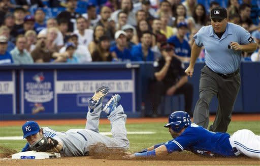 Toronto Blue Jays' Jose Bautista, right, gets forced out at third base by Kansas City Royals third baseman Mike Moustakas, left, during the fifth inning of a baseball game, Tuesday, July 3, 2012, in Toronto. (AP Photo/The Canadian Press, Nathan Denette)