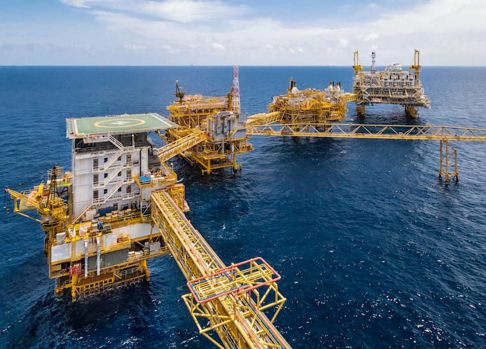 Oil rig with Oil and gas industry platform for produced crude oil, natural gas and produced water in offshore or gulf, petroleum field. The picture was taken in bird eyes view on helicopter or chopper.