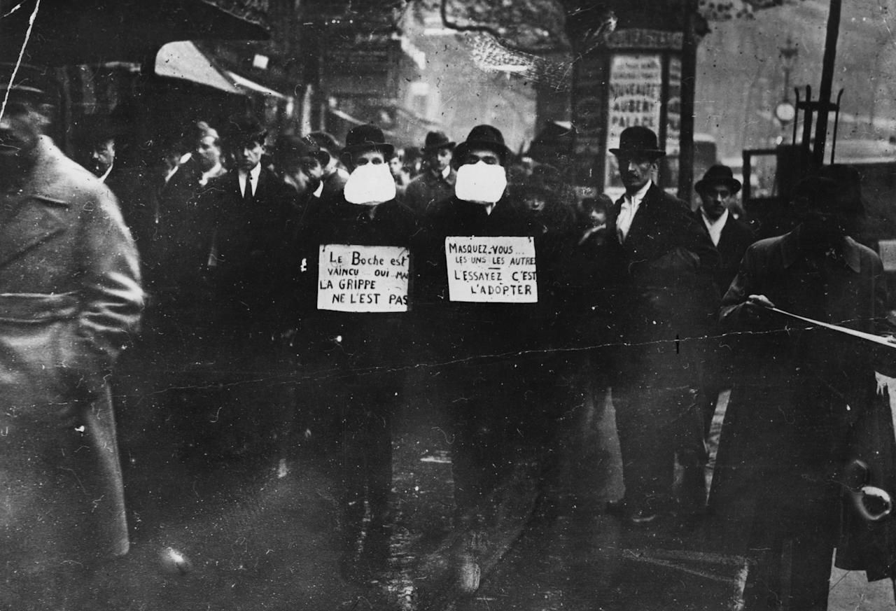1st March 1919:  Two men wearing and advocating the use of flu masks in Paris during the Spanish flu epidemic which followed World War I.  (Photo by Topical Press Agency/Getty Images)