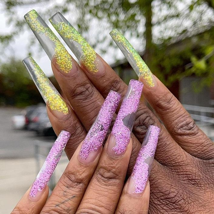 """<a href=""""https://www.allure.com/story/jelly-nail-art-manicure-trend?mbid=synd_yahoo_rss"""" rel=""""nofollow noopener"""" target=""""_blank"""" data-ylk=""""slk:Jelly nails"""" class=""""link rapid-noclick-resp"""">Jelly nails</a> grew in popularity during 2019 and for good reason: They're super cute and allow you to play around with different colors and styles. This set from Taylor is a clear set with a glitter twist. On one hand, she swirled purple glitter across the nails to create a loopy effect, and she did something similar on the other hand, but with yellow shimmers instead."""