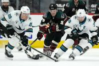 San Jose Sharks right wing Timo Meier, left, controls the puck as Arizona Coyotes right wing Christian Fischer, center, and Sharks center Logan Couture, right, arrive late during the third period of an NHL hockey game Saturday, Jan. 16, 2021, in Glendale, Ariz. The Coyotes defeated the Sharks 5-3. (AP Photo/Ross D. Franklin)