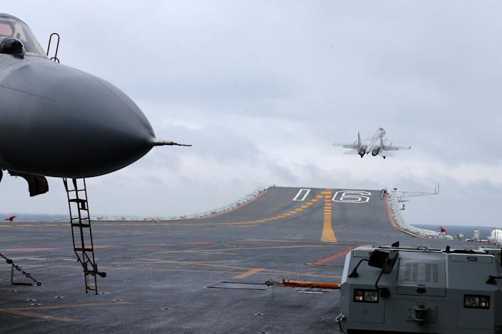J-15 fighters from China's Liaoning aircraft carrier conduct a drill in an area of South China Sea