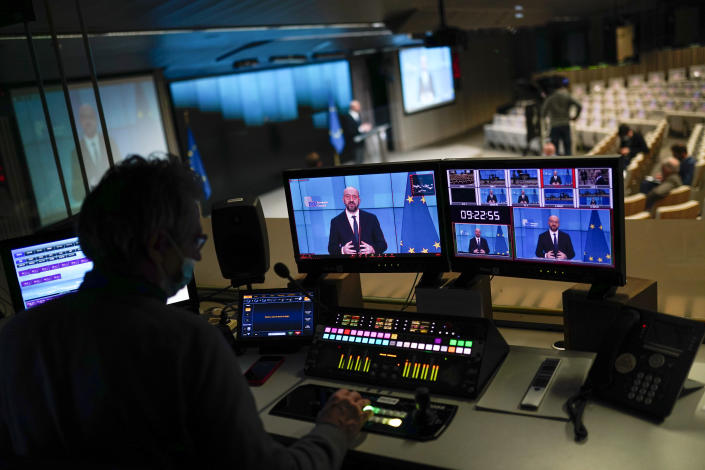 European Council President Charles Michel, displayed in screens, speaks during an online joint press conference with Director General of the World Health Organization Tedros Adhanom Ghebreyesus at the European Council headquarters in Brussels, Tuesday, March 30, 2021. (AP Photo/Francisco Seco, Pool)