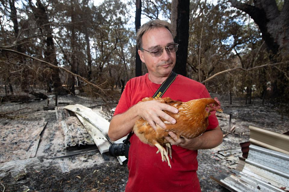 Resident Thorsten Kels with one of his surviving chickens Emma, at Lake Cooroibah Road, Noosa.