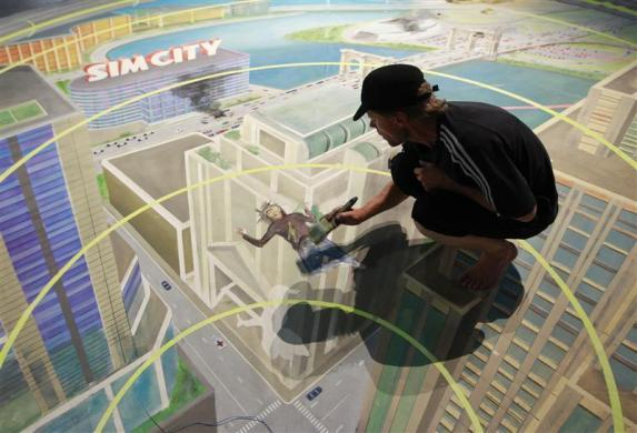 "A worker paints at the exhibition stand of ""Sim City"" during the Gamescom 2012 fair in Cologne August 15, 2012."
