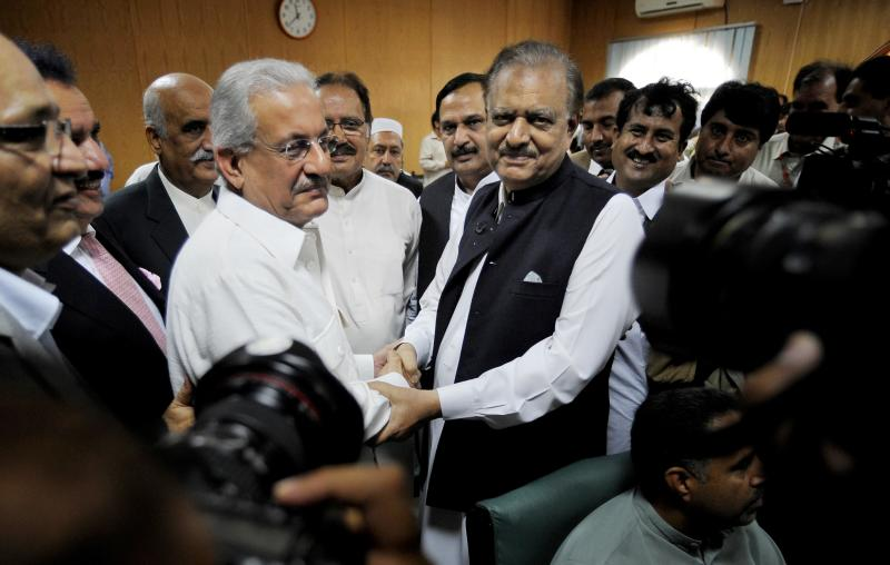 Mamnoon Hussain, center right, a candidate from ruling party Pakistan Muslim League-N shakes hands with Raza Rabbani, a candidate from opposition party Pakistan People Party after submitting their nomination papers for upcoming presidential election in Islamabad, Pakistan, Wednesday, July 24, 2013. Pakistani political parties have nominated their candidates for the upcoming presidential elections with the ruling party's candidate seen as the front-runner. (AP Photo/Anjum Naveed)