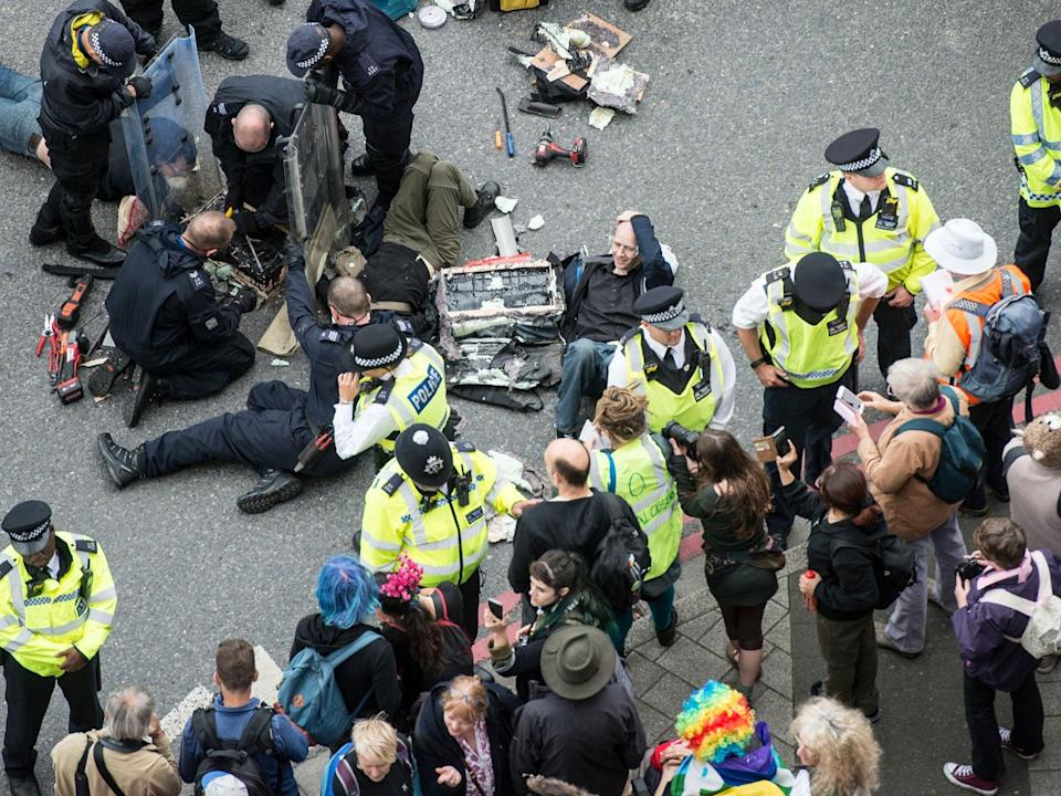 Police work to remove protesters who blocked an access road to the 2017 Defence and Security Equipment International (DSEI) arms fair by chaining themselves together on 6 September 2017 (Getty Images)