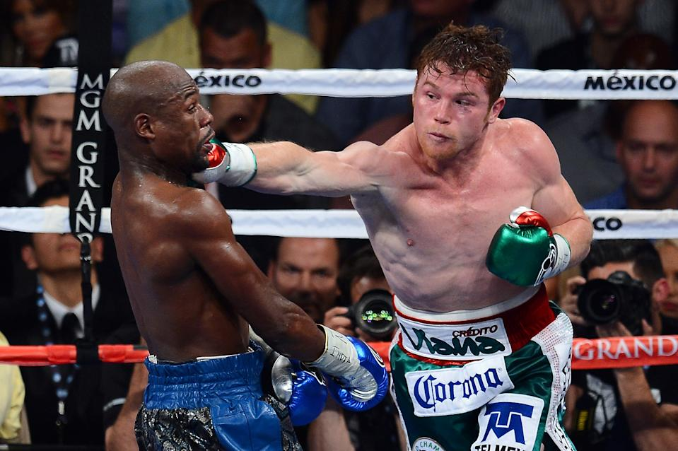 LAS VEGAS, NV - SEPTEMBER 14:  (R-L) Canelo Alvarez throws a right at Floyd Mayweather Jr. during their WBC/WBA 154-pound title fight at the MGM Grand Garden Arena on September 14, 2013 in Las Vegas, Nevada.  (Photo by Ethan Miller/Getty Images)