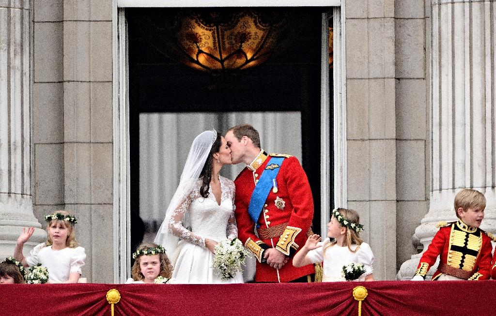 Prince William kisses his wife Kate on the balcony of Buckingham Palace after their wedding (AFP Photo/LEON NEAL)