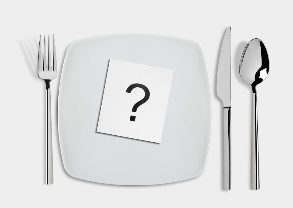 Question mark in  white square plate and fork,spoon and table knife isolated on white background. Conceptual image.
