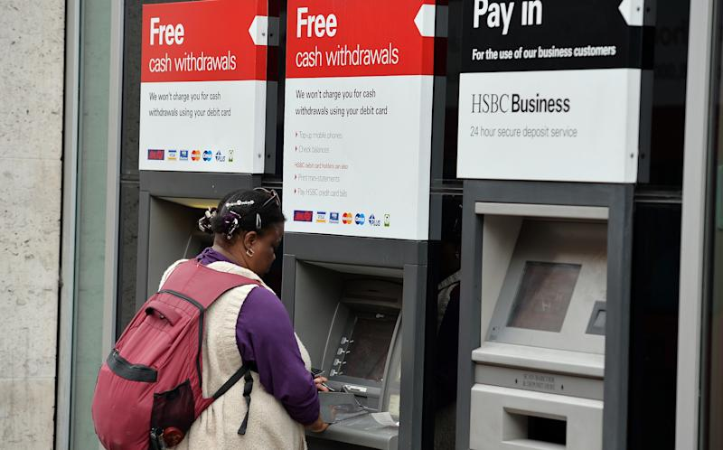 A person uses a cash machine at a HSBC branch in London as the banking giant is to cut between 22,000 and 25,000 jobs globally including a reported 8,000 in the UK as part of an overhaul to slash costs and reshape the business.