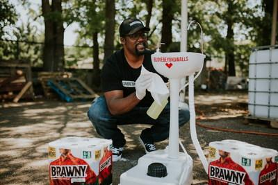 Giant Terence Lester, Founder of Love Beyond Walls, cleans one of many portable handwashing stations that he sets out for Atlanta's homeless.