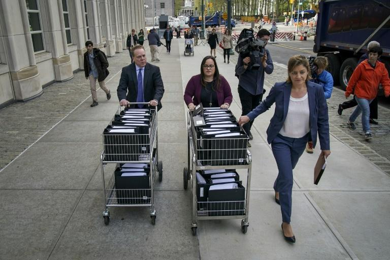 Officials with the US Attorney's Office of the Eastern District of New York push carts full of court documents related to Keith Raniere's case outside of court in Brooklyn in May 2019