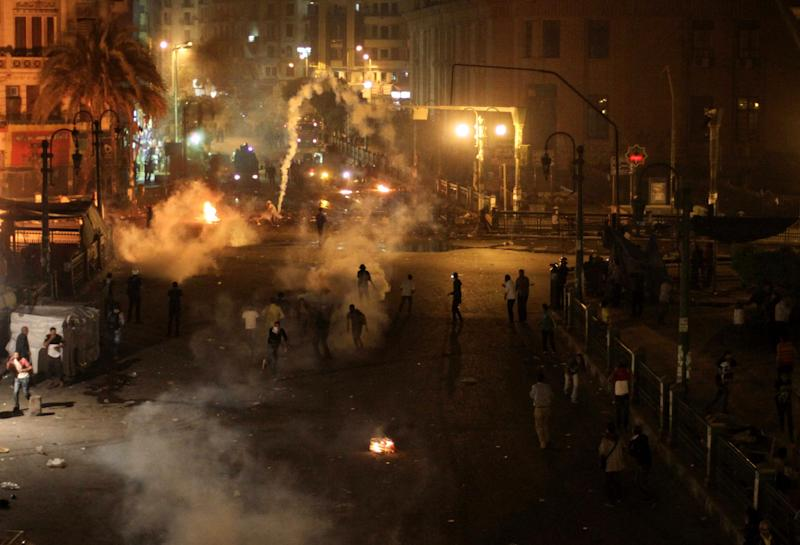 Tear gas fills downtown as protesters clash with security forces in downtown Cairo, Egypt, Saturday, April 6, 2013. Police fired tear gas at hundreds of protesters outside the chief prosecutor's office Saturday in central Cairo who were pushing on the building's doors demanding he resign.(AP Photo/Mostafa Elshemy)