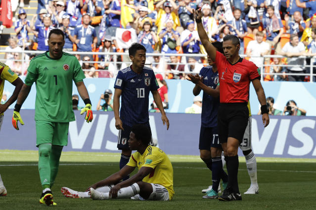 Referee Damir Skomina from Slovenia shows the red card to Colombia's Carlos Sanchez, bottom, during the group H match between Colombia and Japan at the 2018 soccer World Cup in the Mordavia Arena in Saransk, Russia, Tuesday, June 19, 2018. (AP Photo/Eugene Hoshiko)