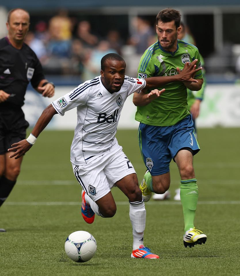 SEATTLE, WA - AUGUST 18:  Dane Richards #20 of the Vancouver Whitecaps dribbles against Brad Evans #3 of the Seattle Sounders FC at CenturyLink Field on August 18, 2012 in Seattle, Washington.  (Photo by Otto Greule Jr/Getty Images)