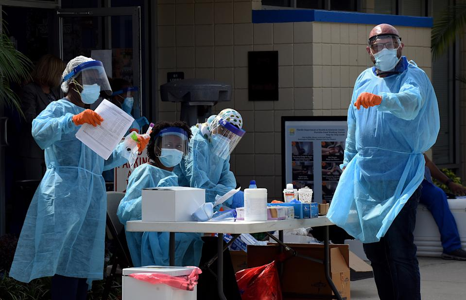 Health workers are seen at a mobile COVID-19 testing site in the Goldsboro neighborhood of Sanford, Fla., on April 23, 2020. Local health officials offered the free tests at six historic Black communities in Seminole County to help residents who are not only especially vulnerable to coronavirus, but who cannot drive to a health clinic or may be unable to afford health insurance. (Photo by Paul Hennessy/NurPhoto via Getty Images)
