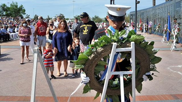 <p>As a wreath is placed for her husband Christopher Colafati, Marissa Coafati stands with her sons Xavier, 3, from left, and Damien, 6, and father-in-law Frank Colafati, Jr. during Jacksonville's annual Memorial Day observance held at the Veterans Memorial Wall on Monday, May 29, 2017. The 65-foot-long monument and eternal flame serves as a tribute to almost 1,700 of Jacksonville's fallen veterans. (Photo: Bruce Lipsky/The Florida Times-Union via AP) </p>
