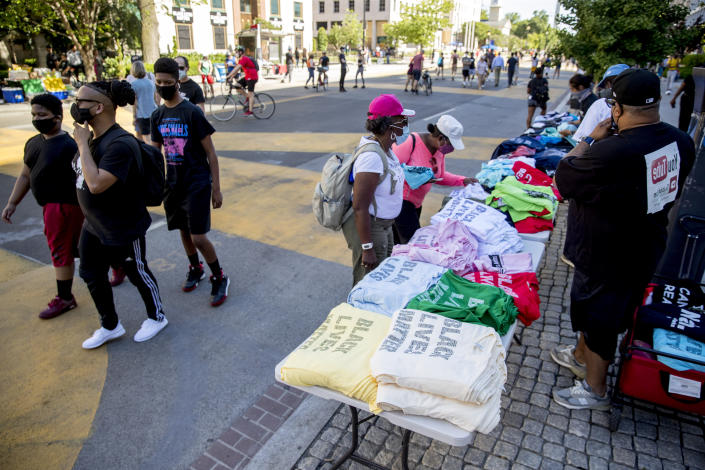 A man sells shirts on 16th Street, Monday, June 8, 2020, near the White House in Washington, after days of protest over the death of George Floyd, a black man who was in police custody in Minneapolis. Floyd died after being restrained by Minneapolis police officers. (AP Photo/Andrew Harnik)