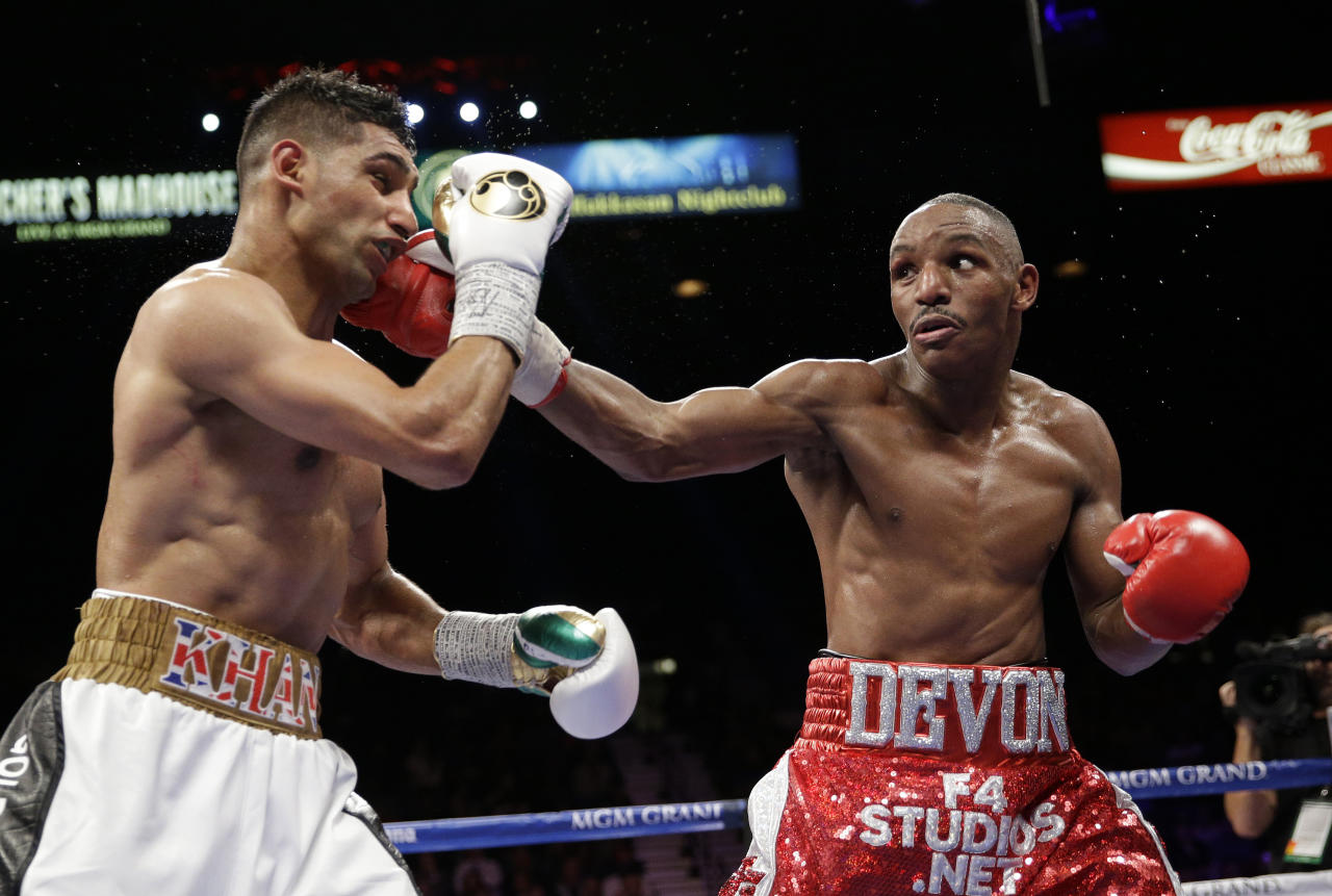 Devon Alexander punches Amir Khan during their welterweight bout Saturday, Dec. 13, 2014, in Las Vegas. (AP Photo/John Locher)