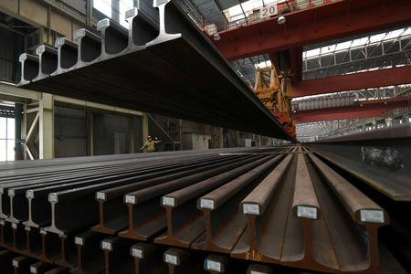 FILE PHOTO: A worker directs a crane lifting steel rails at a steel factory in Handan