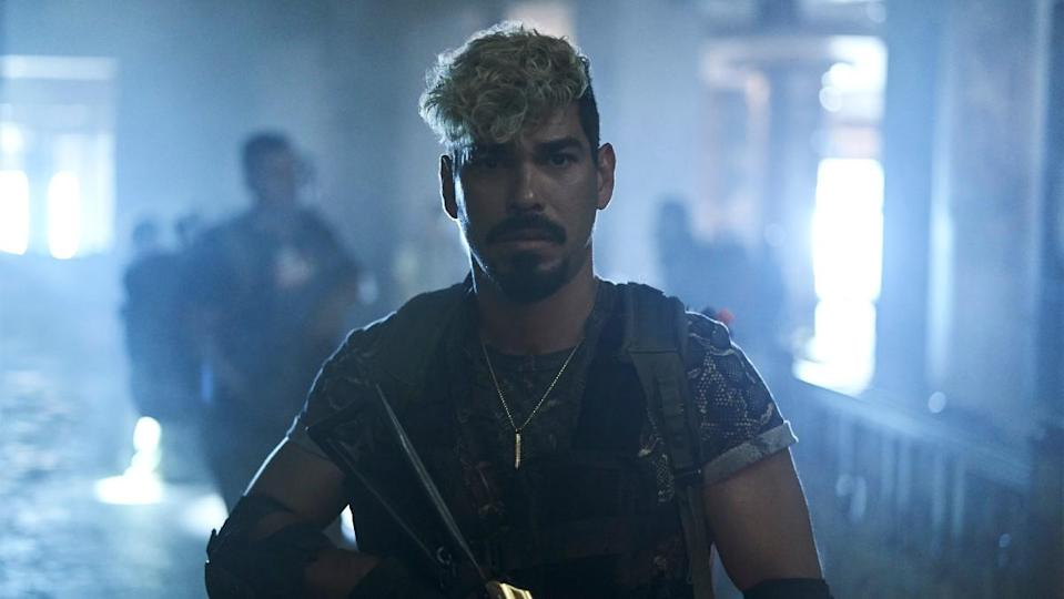 Raúl Castillo as Mikey Guzman looks at the camera and carries a weapon in a still from Army of the Dead.