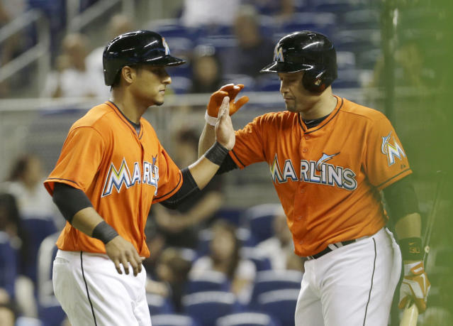 Miami Marlins' Donovan Solano, left, is congratulated by teammate Placido Polanco after Solano scored on a walk with the bases loaded by Philadelphia Phillies relief pitcher Luis Garcia in the first inning of a baseball game, Monday, Sept. 23, 2013, in Miami. (AP Photo/Alan Diaz)