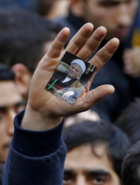 A man raises his hand bearing a portrait of late Iranian former president Akbar Hashemi Rafsanjani during his funeral ceremony in the capital Tehran, on January 10, 2017 (AFP Photo/Atta KENARE)