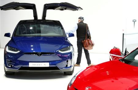 A visitor inspects a Tesla Model X electric vehicle at Brussels Motor Show
