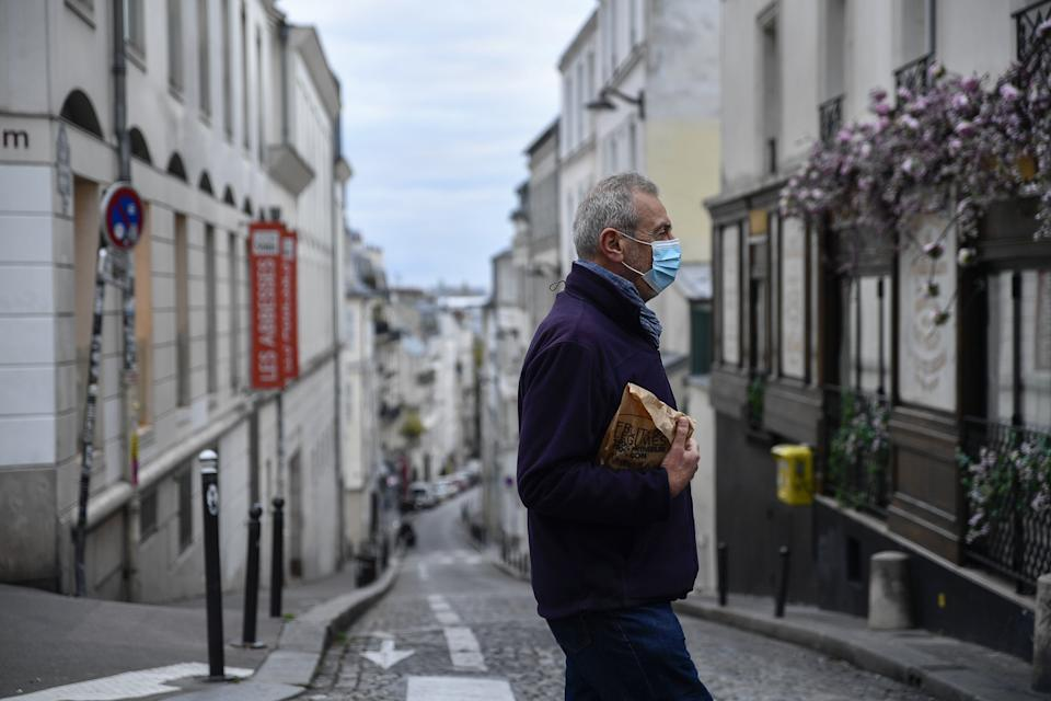 PARIS, FRANCE - OCTOBER 30: A man walks at empty street after France on Friday entered the second national lockdown imposed to stem the spread of the novel coronavirus in Paris, France on October 30, 2020. (Photo by Julien Mattia/Anadolu Agency via Getty Images)