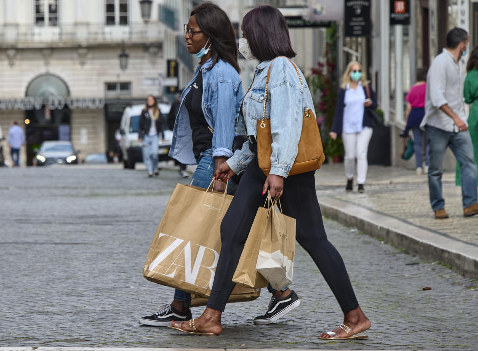 LISBON, PORTUGAL - APRIL 19: Shoppers walk with Zara bags in Rua Garrett on the first day of deconfinement's third phase with shops reopening with limitations and restaurants allowed to serve patrons indoors during the COVID-19 Coronavirus pandemic on April 19, 2021 in Lisbon, Portugal. According to updated data from the General Direction of Health (DGS) Portugal confirmed a total of 831,221 infections and 16,946 deaths since the beginning of the pandemic. The government has relaxed confinement and renewed the country's state of emergency until April 30.  (Photo by Horacio Villalobos#Corbis/Corbis via Getty Images)