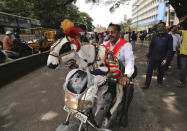 A man rides with a decorated goat on his motorcycle during a protest against farm bills in Bengaluru, India, Monday, Sept. 28, 2020. Indian lawmakers earlier this month approved a pair of controversial agriculture bills that the government says will boost growth in the farming sector through private investments. (AP Photo/Aijaz Rahi)