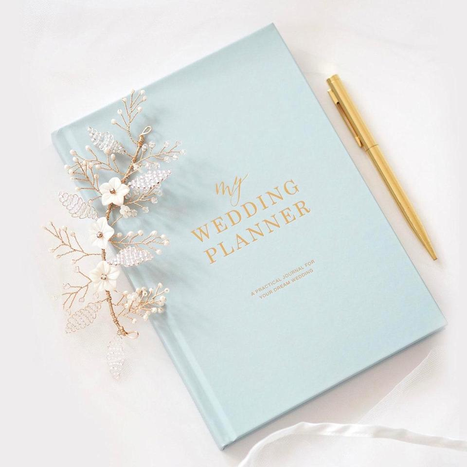 """For all the details they'll likely forget. $41, Etsy. <a href=""""https://www.etsy.com/listing/715275044/luxury-blue-and-gold-wedding-planner"""" rel=""""nofollow noopener"""" target=""""_blank"""" data-ylk=""""slk:Get it now!"""" class=""""link rapid-noclick-resp"""">Get it now!</a>"""