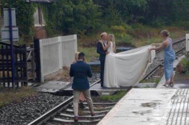 Bride in white dress pictured with groom trespassing on railway line for express wedding