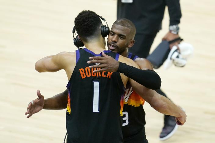 Phoenix Suns' Devin Booker (1) and Chris Paul (3) hug after Game 1 of basketball's NBA Finals against the Milwaukee Bucks, Tuesday, July 6, 2021, in Phoenix. The Suns defeated the Bucks 118-105. (AP Photo/Ross D. Franklin)