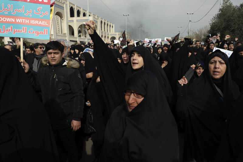 A woman clenches her fist as she chants slogan while a man holds an anti-Israeli placard during a demonstration over the U.S. airstrike in Iraq that killed Iranian Revolutionary Guard Gen. Qassem Soleimani in Tehran, Iran, Jan. 3, 2020. Iran has vowed