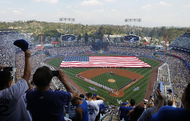 "An American flag covers the field at Dodger Stadium during the singing of the national anthem on opening day 2016. <span class=""copyright"">(Christina House / Los Angeles Times)</span>"