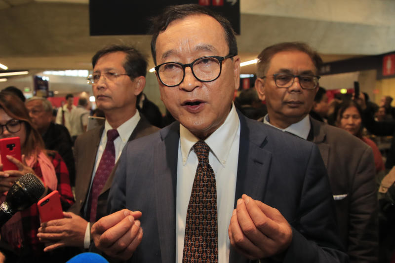 Cambodia's most prominent opposition politician Sam Rainsy answers reporters as he is attempting to return to Cambodia Thursday, Nov. 7, 2019 at Charles de Gaulle airport, north of Paris. Sam Rainsy is attempting to return to Cambodia from his self-imposed exile to force out the long-serving leadership but may not be let on Thursday's Paris-Bangkok flight. (AP Photo/Michel Euler)