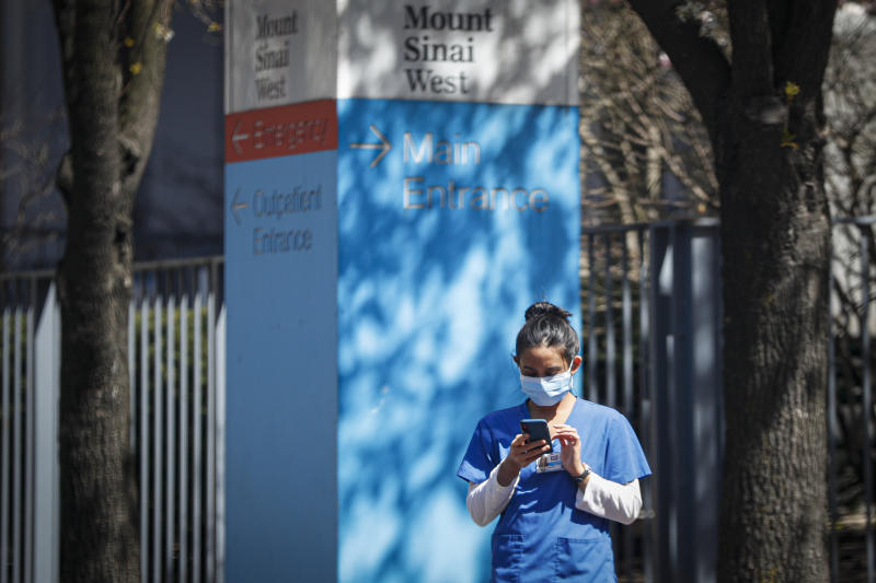 A medical worker uses her phone while wearing a surgical mask outside Mt. Sinai West, Thursday, March 26, 2020, in New York. The new coronavirus causes mild or moderate symptoms for most people, but for some, especially older adults and people with existing health problems, it can cause more severe illness or death. (AP Photo/John Minchillo)