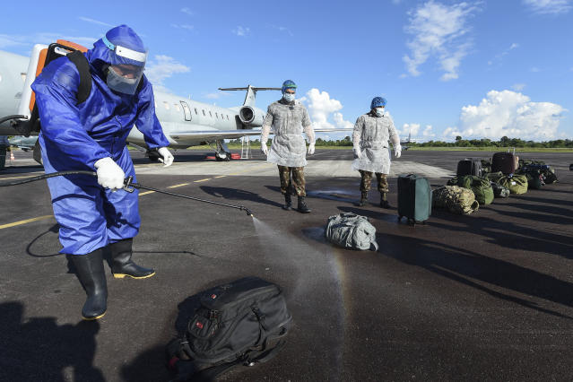 Members of the Brazilian Armed Forces disinfect luggage that arrived on a military flight at the airport, in Tabatinga, Amazonas state, northern Brazil, on June 17, 2020, to assist indigenous population amid the COVID-19 pandemic. - As the new coronavirus has ravaged Brazil, more than 7,000 indigenous people have contracted the virus, and more than 300 have died, according to the Brazilian Indigenous Peoples' Association (APIB), forcing many indigenous groups to take matters into their own hands. Some have locked the world out, banning outsiders and putting up a makeshift roadblock at the entrance to their territory, while others have fled into the jungle. (Photo by EVARISTO SA / AFP) (Photo by EVARISTO SA/AFP via Getty Images)