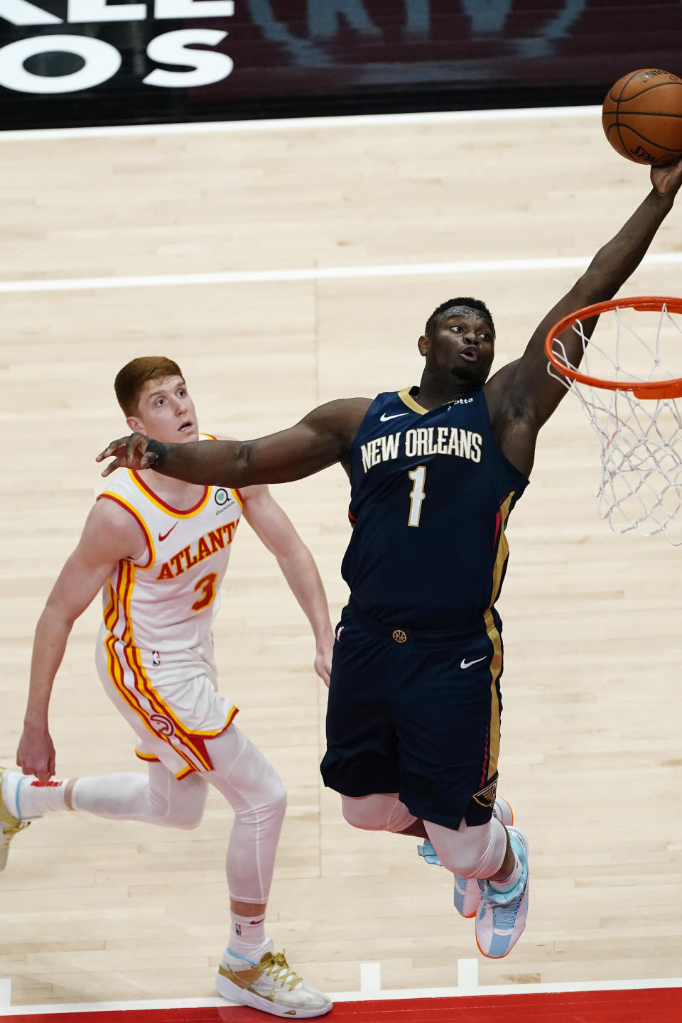 New Orleans Pelicans forward Zion Williamson (1) scores as Atlanta Hawks guard Kevin Huerter (3) defends in the first half of an NBA basketball game Tuesday, April 6, 2021, in Atlanta. (AP Photo/John Bazemore)