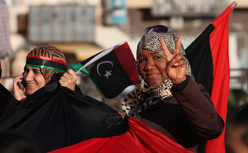 FILE - In this Sunday, Feb. 17, 2013 file photo, a Libyan woman flashes the victory sign at Tahrir Square, during the second anniversary of the uprising that toppled longtime dictator Moammar Gadhafi in Benghazi, Libya. Women played a major role in the 8-month civil war against dictator Moammar Gadhafi, massing for protests against his regime, selling jewelry to fund rebels, helping treat the wounded, smuggling weapons across enemy lines to rebels. But since Gadhafi's fall more than 18 months ago, women have been rewarded by seeing rights they enjoyed under his rule hemmed in and restricted. (AP Photo/Mohammad Hannon, File)