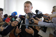 Romanian President Klaus Iohannis speaks to media after casting his vote in Bucharest, Romania, Sunday, Nov. 10, 2019. Voting got underway in Romania's presidential election after a lackluster campaign overshadowed by a political crisis which saw a minority government installed just a few days ago. (AP Photo/Vadim Ghirda)