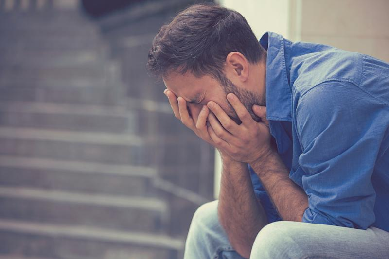 Man sitting on a step in a blue shirt crying