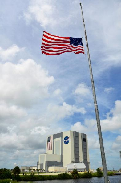 The U.S. flag flies at half mast outside the Vehicle Assembly Building in honor of Neil Armstrong at the Kennedy Space Center, August 31, 2012 in Cape Canaveral, Florida. Armstrong, the first man to walk on the moon, died from complications from heart surgery at the age of 82. (Photo by Roberto Gonzalez/Getty Images)